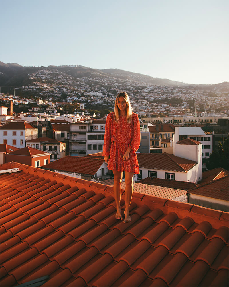 Me stood on the roof at the Hotel in madeira at sunrise with Funchal behind