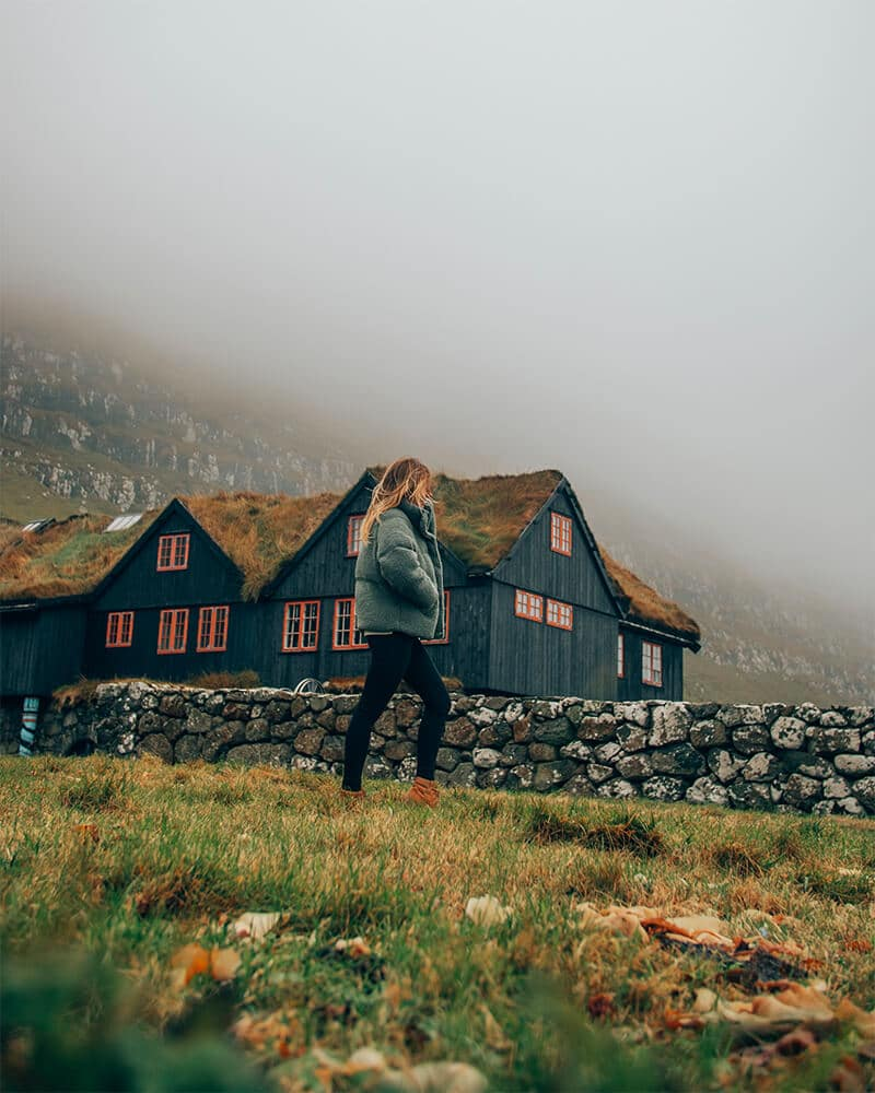 Me walking in front of a traditional Faroese house with a grass top roof
