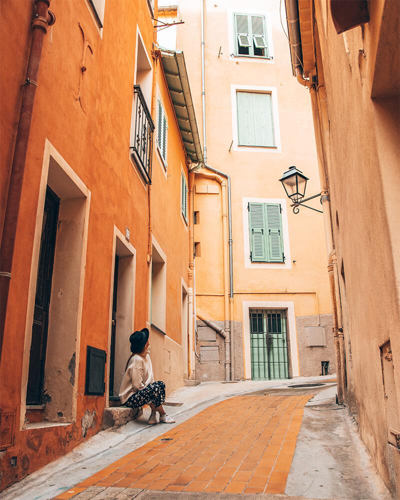 Me sat on a little orange street in Menton