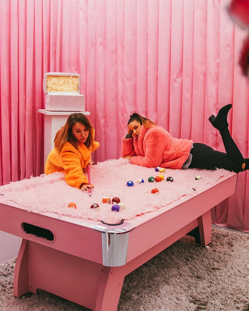 Two girls on a pink fluffy pool table at WONDR Experience Amsterdam
