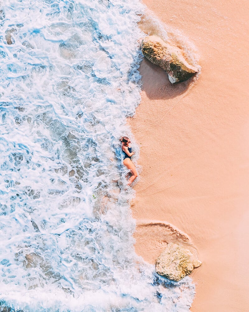 A drone shot of me on the beach with sand and waves crashing against my back at Green Bowl Beach Bali