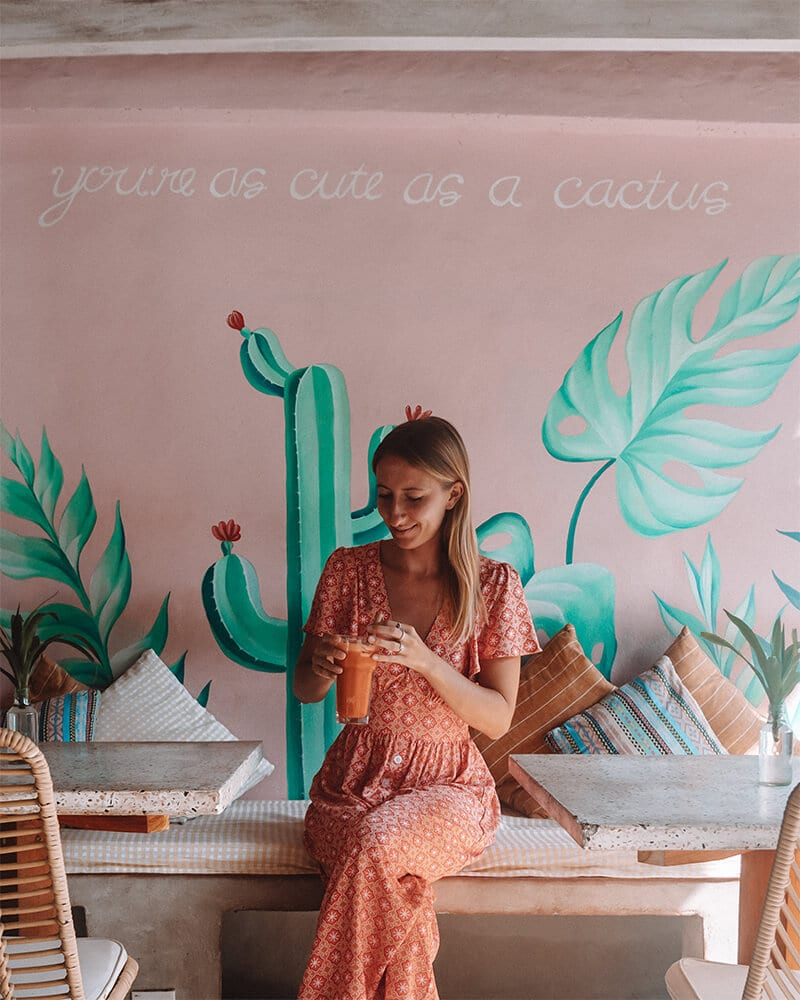 Me sat in front of a pink instagrammable wall in a cafe on Nusa penida - Secret Penida Cafe