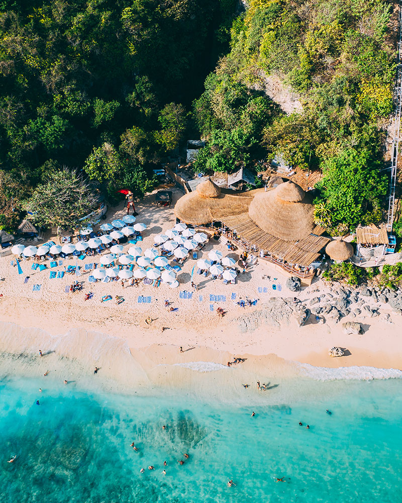 Drone shot of Karma Beach Bali with a beach club, blue water and umbrellas on the beach