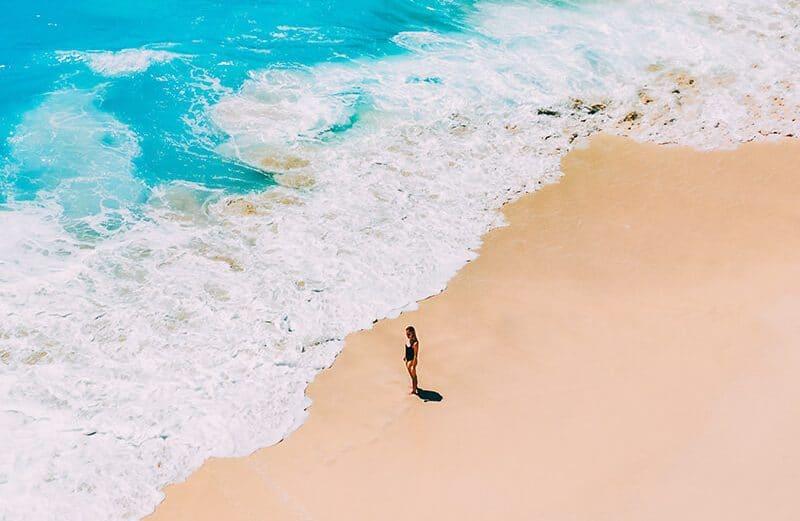 Girl standing on the beach at Kelingking Beach, Nusa Penida