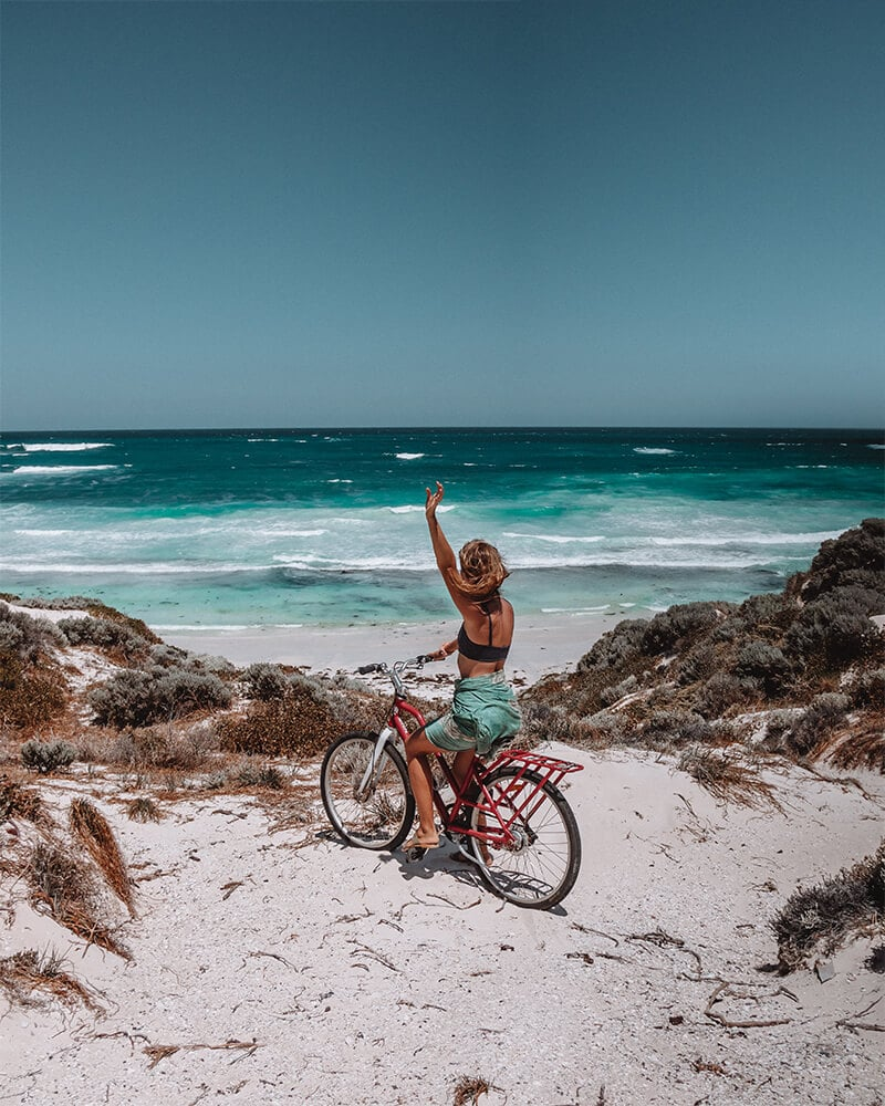 Me sat on a bike overlooking the sea with one arm up at Rottnest Island!