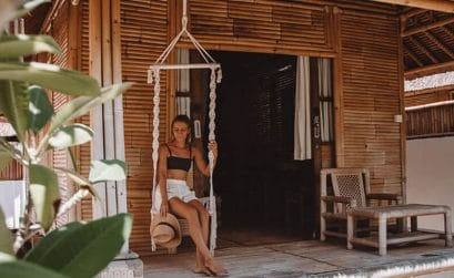 Girl sat on a swing outside a bamboo bungalow on Nusa Lembongan Island, Bali, Indonesia