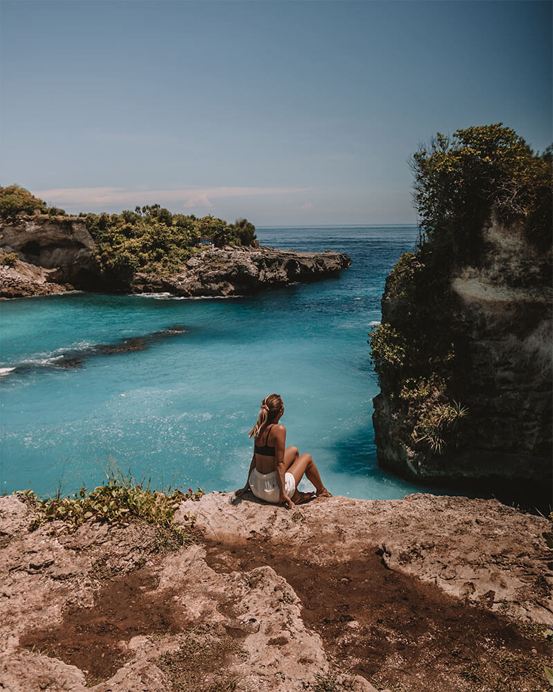 Girl sat in front of bright blue water at the Blue Lagoon on Nusa Ceningan