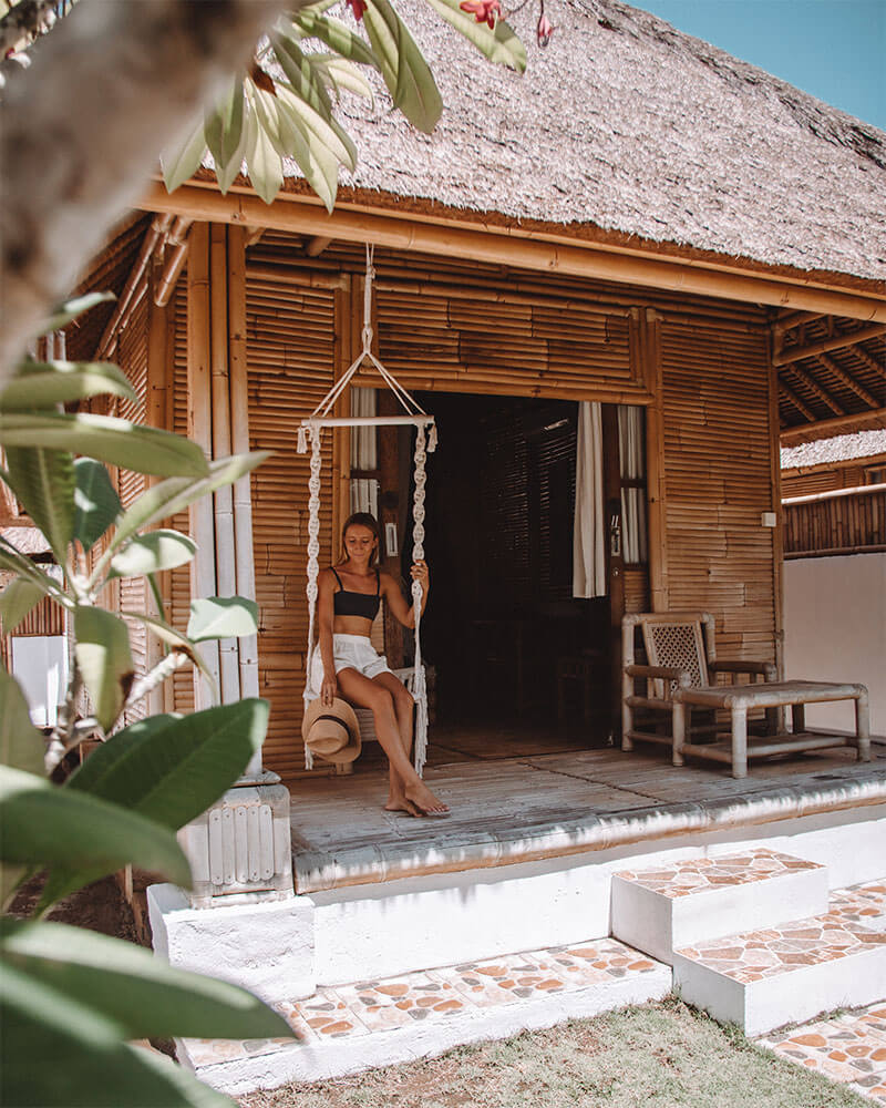 Girl sitting on a swing in front of a bamboo bungalow holding a hat - the best place to stay on Nusa Lembongan Island, Bali
