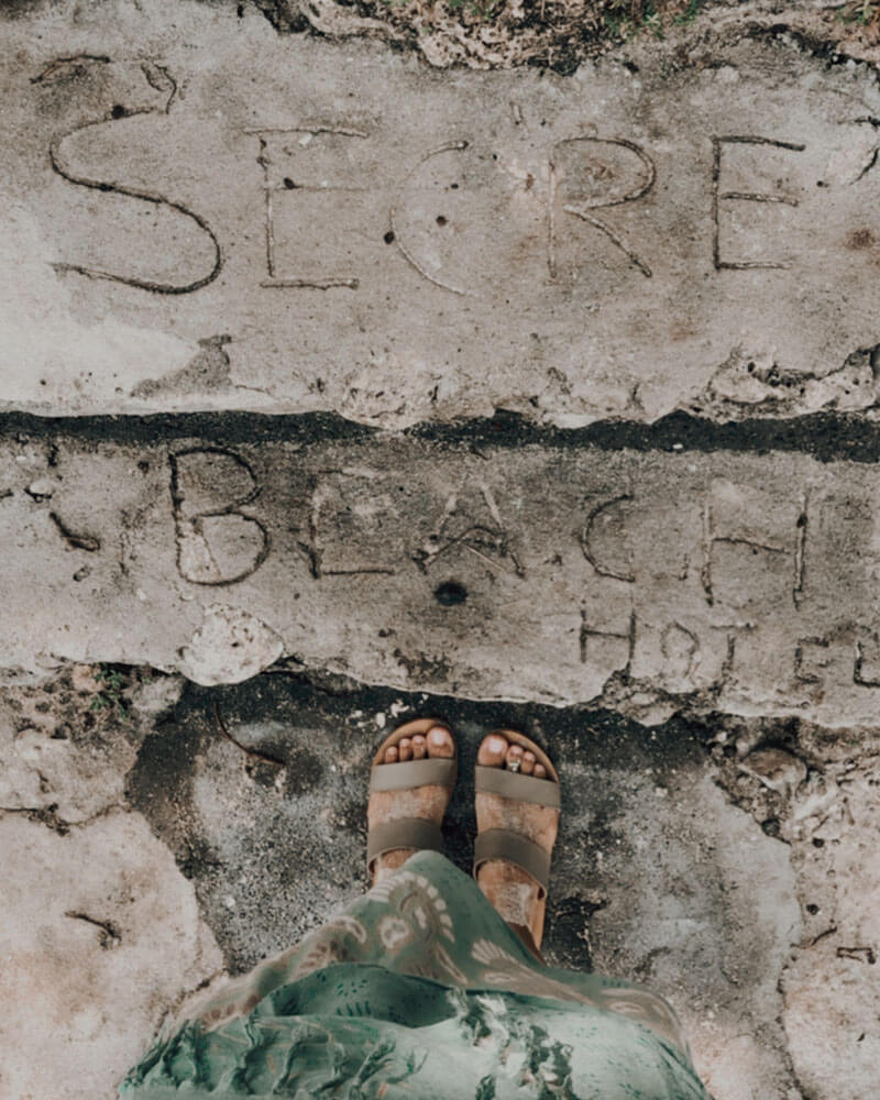 Feet and an engraved sign saying Secret Beach on Nusa Ceningan