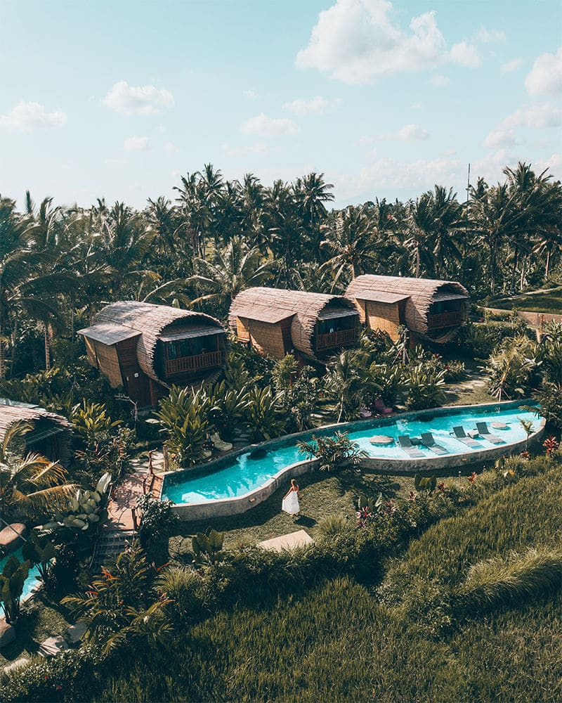 Drone shot of a girl walking through an instagrammable hotel in Bali - one of the unique places to stay in Ubud! Adiwana Bee House