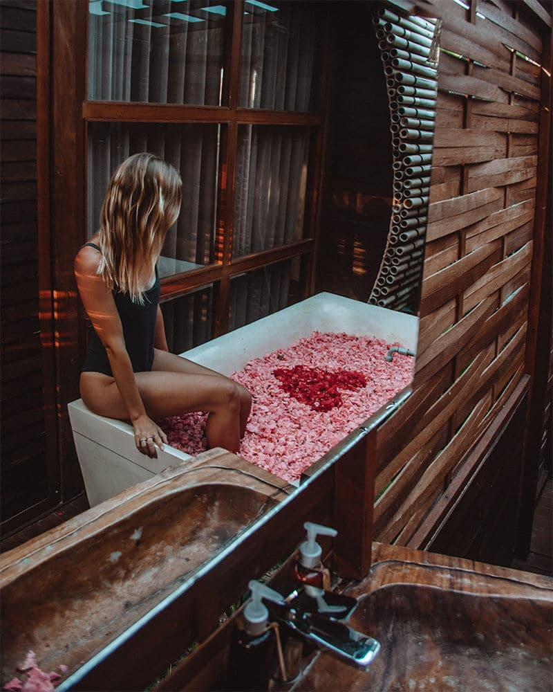 Girl sat on the edge of a flower bath in Bali, pink petals and one of the most unique places to stay in Ubud!