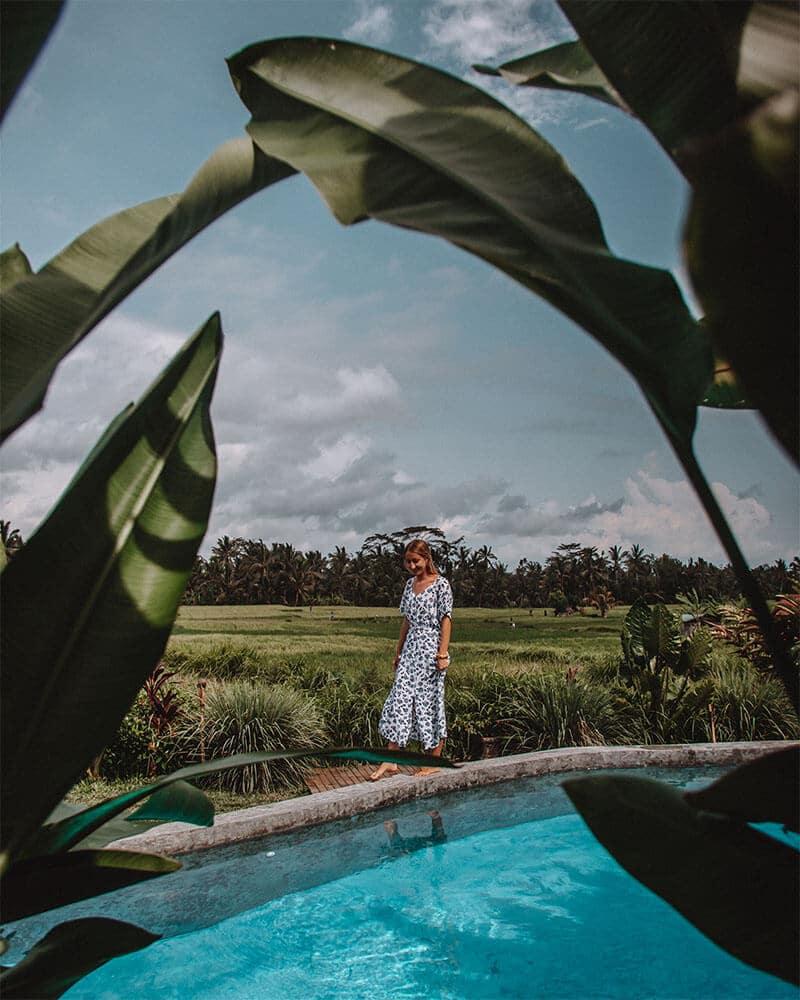 Girl walking along the edge of an infinity pool in Ubud, Bali. Adiwana Bee House