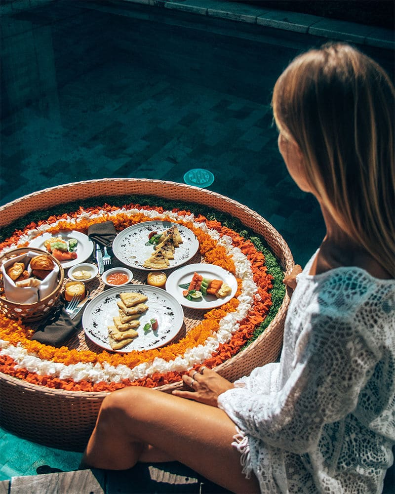Girl sat with a floating breakfast in the pool at a unique place to stay in Bali - Adiwana Arkara Villa