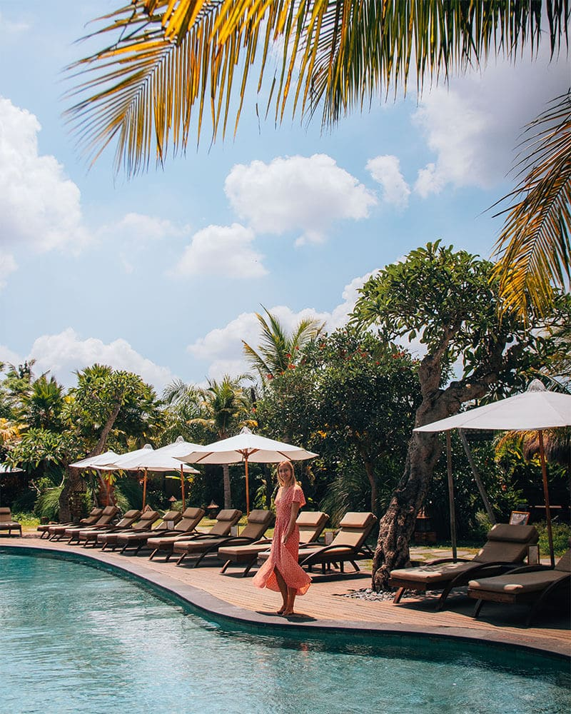 Girl walking along the edge of a pool with a palm tree and blue sky - Adiwana Arya Villa in Ubud, bali. An instagrammable hotel in Bali