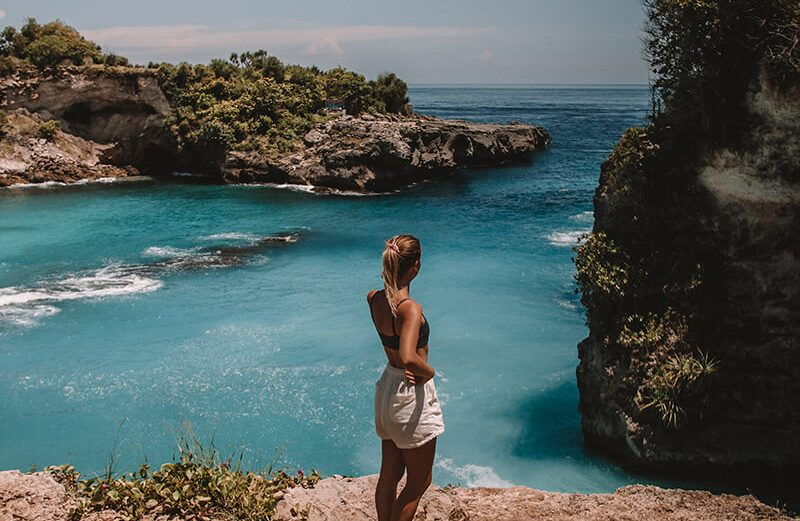 Me stood overlooking the blue lagoon at Nusa Ceningan with blue water and wearing a bikini top and shorts in Bali Indonesia