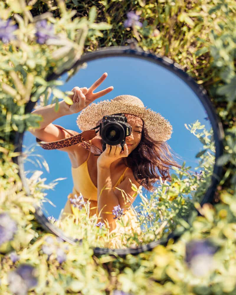 Jasmine Alley taking creative mirror photography outside with the flowers!