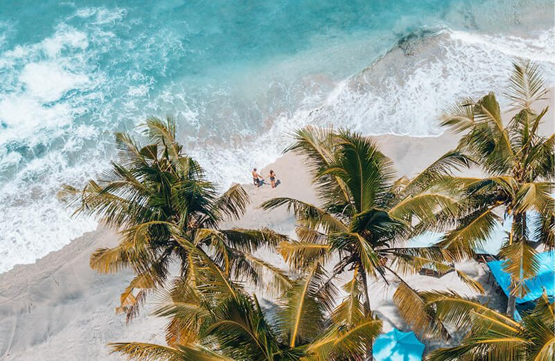 Couple drone photography ideas on the beach with palm trees and sea and sand in Bali