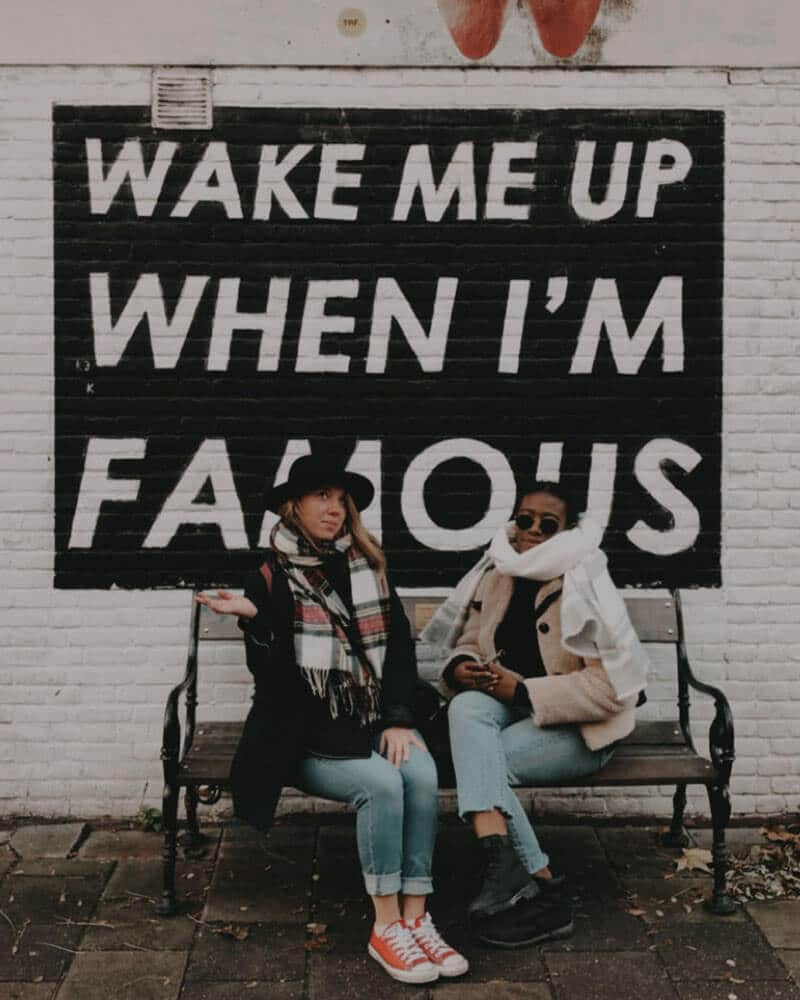 Two girls sat in front of the 'Wake me up when I'm famous' sign in Amsterdam - one of the alternative things to do in Amsterdam