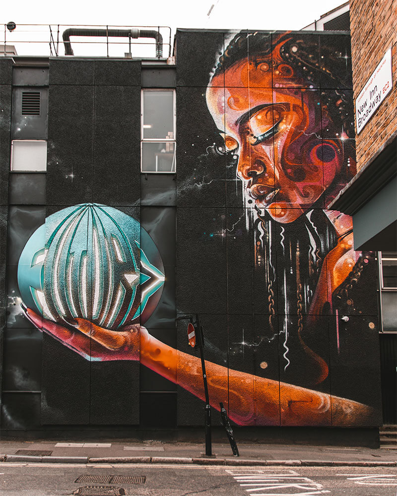 London Street Art - woman holding round object at New Inn Yard