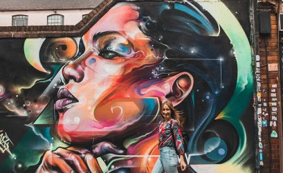 Solarpoweredblonde stood in front of a street art mural on Fashion Street, East London Street Art