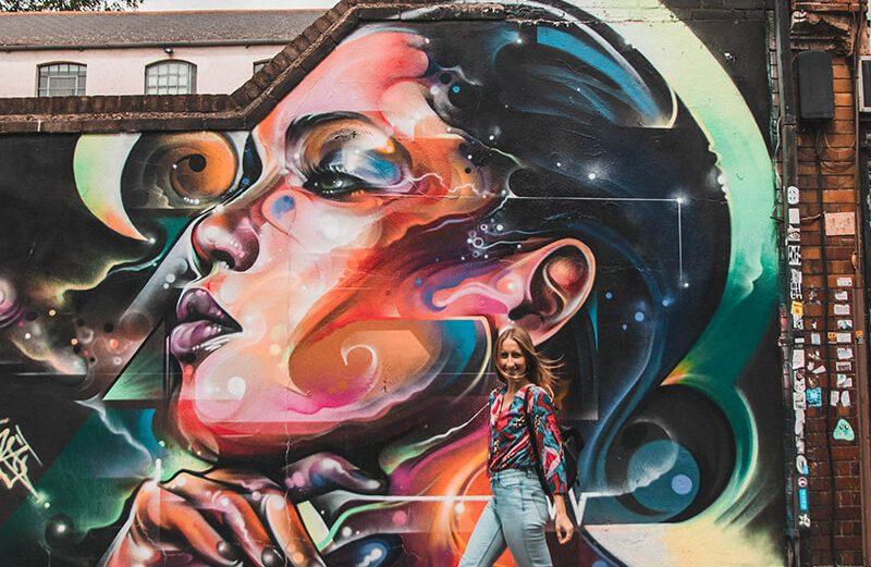 Solarpoweredblonde stood in front of a street art mural on Fashion Street, East London Street Art