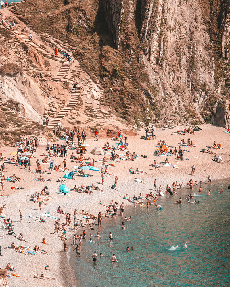 People sat on the beach at Durdle Door in Dorset England