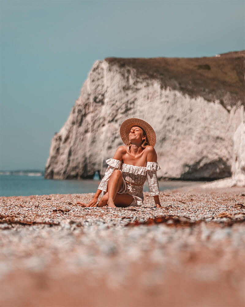 Solarpoweredblonde sat on the beach at Durdle Door in a hat and dress