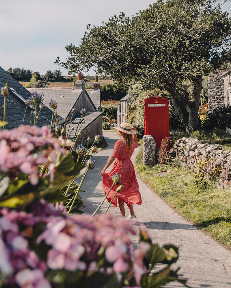 Solarpoweredblonde walking down a path on St Martins island with a red dress on and a red phone box
