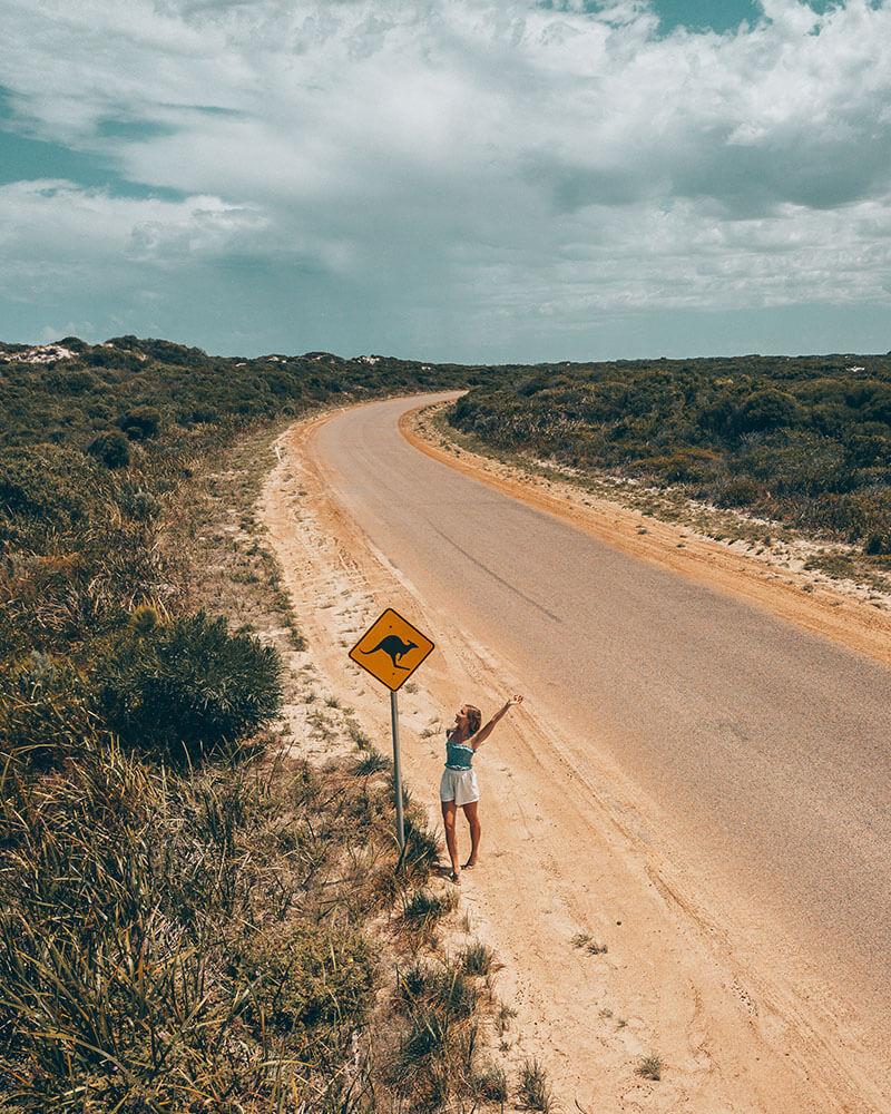 Solarpoweredblonde standing next to a kangaroo sign