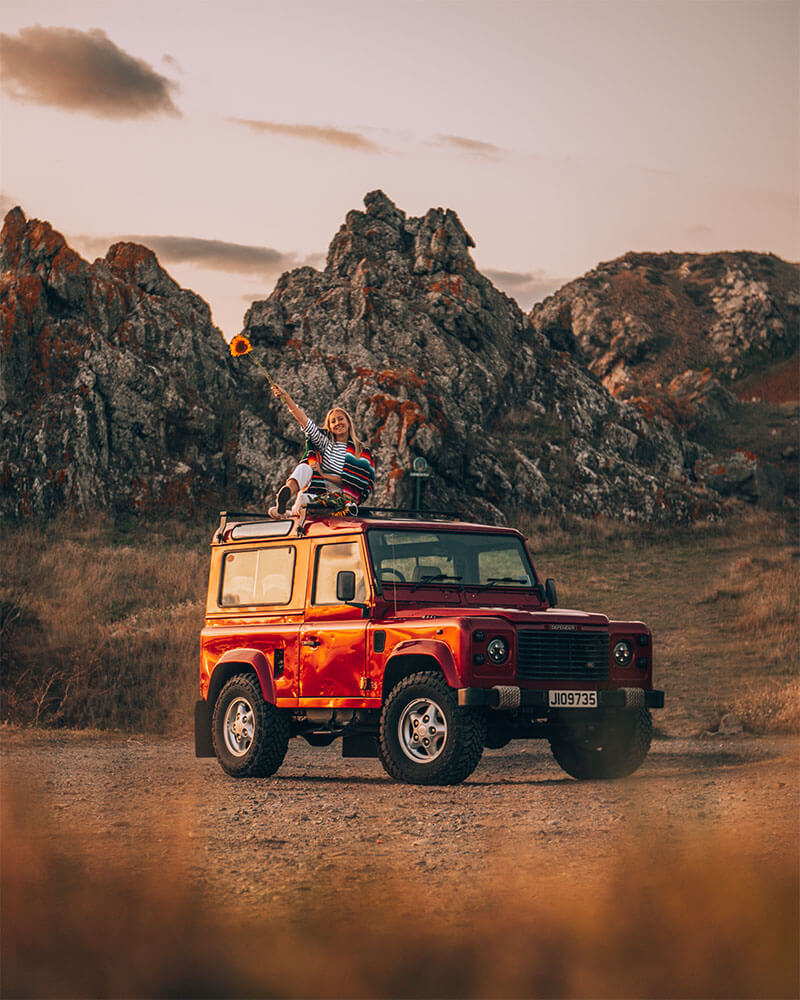 Solarpoweredblonde sat on top of a jeep in Jersey Channel Islands - travel photography tips and ideas