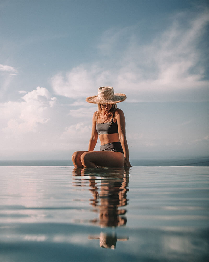 Solarpoweredblonde sat on the side of an infinity pool in Bali with a straw hat on - travel photography tips and ideas