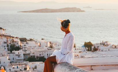 Solarpoweredblonde sat at a sunset viewpoint in Mykonos - travel photography tips and ideas