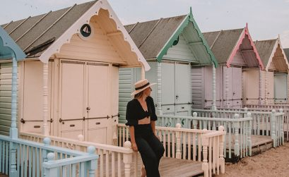 West Mersea Island beach huts - Solarpoweredblonde sat in front of pastel coloured beach huts in Essex UK