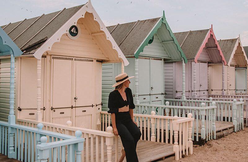 West Mersea Island beach huts - Solarpoweredblonde sat in front of pastel coloured beach huts in Essex UK