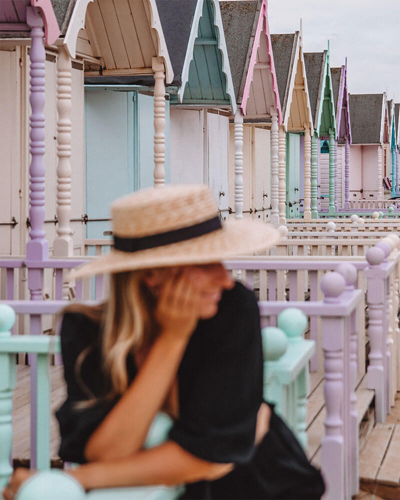 Solarpoweredblonde in front of the colourful pastel coloured beach huts on Mersea island UK