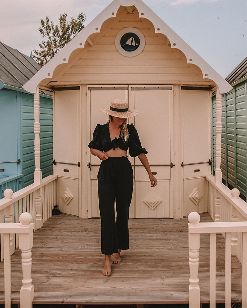 Solarpoweredblonde wearing black stood in front of a Mersea Island beach hut