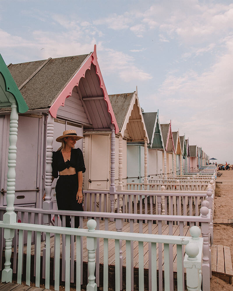 Solarpoweredblonde in front of colourful pastel beach huts in Mersea island Essex