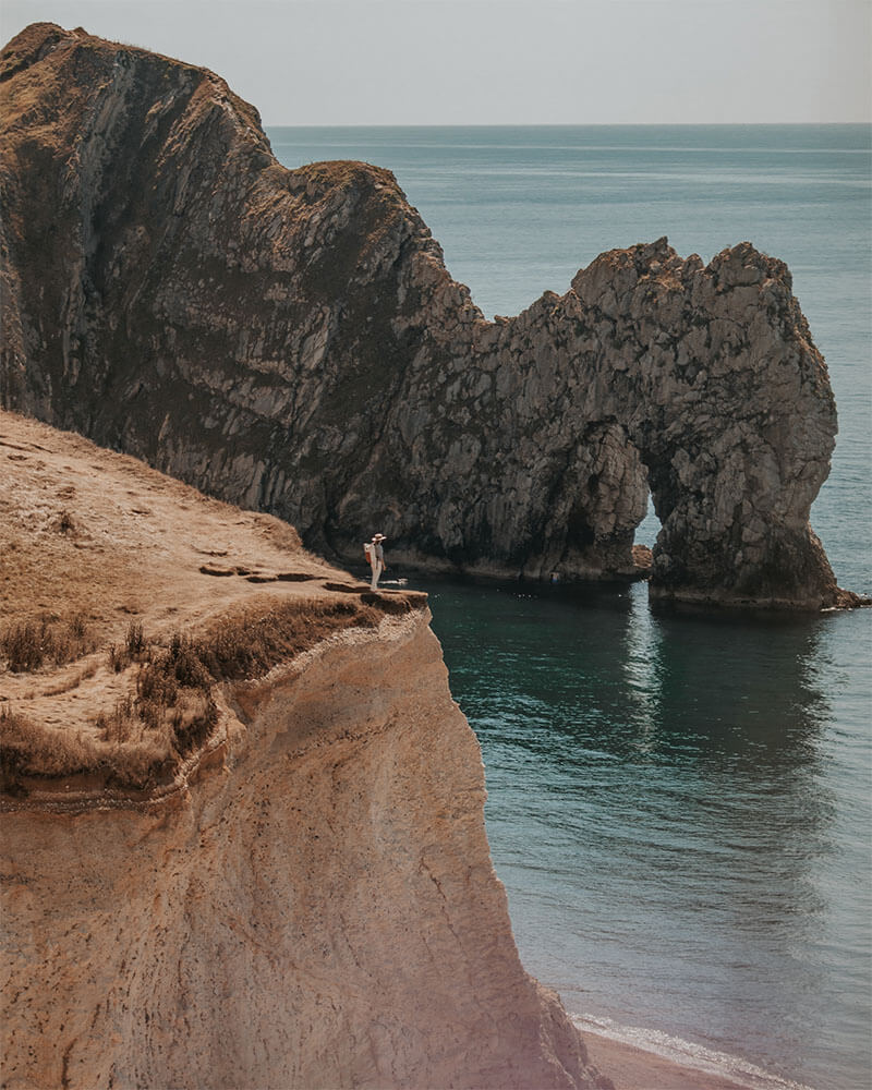 Solarpoweredblonde stood on a cliff at Durdle Door UK - the best camera for travel photography