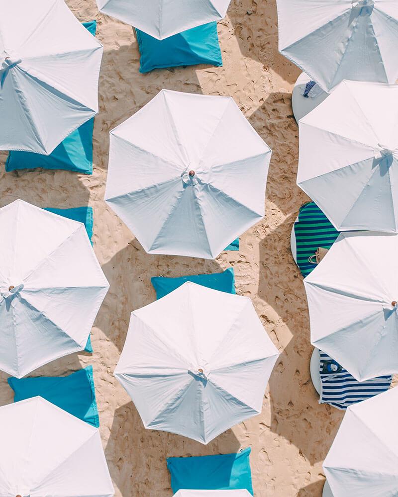 Drone shot of Karma Beach Bali umbrellas on the sand
