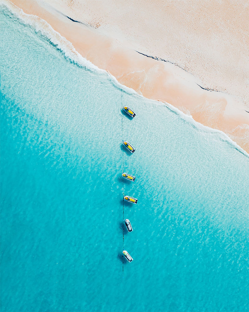 Drone shot of a few jet skis in a row on blue sea and perfect sand in the Caribbean island