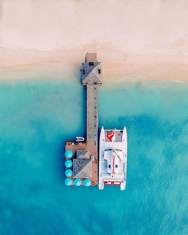 A pier near a hotel in Aruba with perfect blue sea and white sand - drone shot by @boyanoo