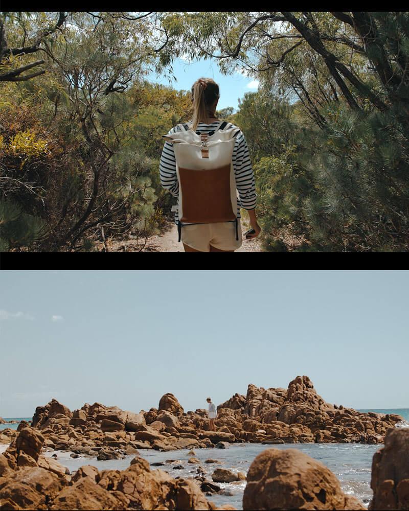 Hanna walking along rocks wearing a backpack