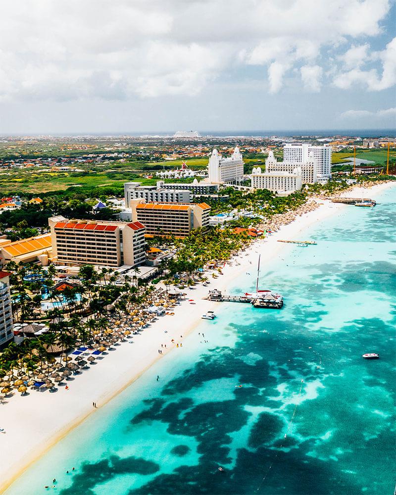 Drone shot of the blue sea and sand on Palm Beach Aruba